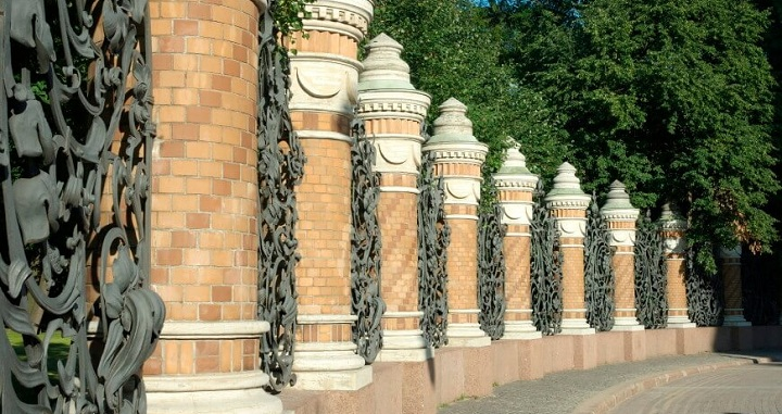 A Very Ornate Wrought Iron Pattern Between Brick Pillars