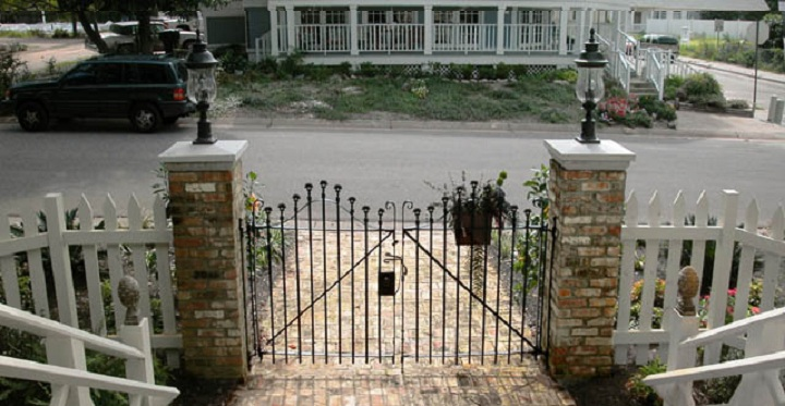 Wood Posts with Attached Wrought Iron Fencing Over a Brick Curb
